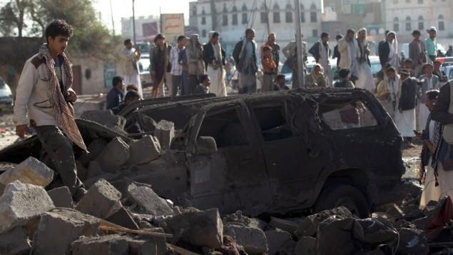 يمنيون يقفون في موقع استهدفته غارة سعودية ضد المتمردين الحوثيين بالقرب من مطار صنعاء في 26 مارس، 2015، ما أسفر عن مقتل 13 شخصا على الأقل. (AFP/MOHAMMED HUWAIS)