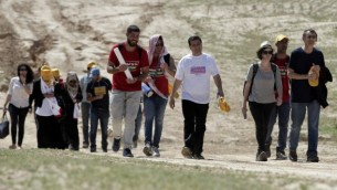 رئيس القائمة المشتركة أيمن عودة، بالقميص الأبيض، وعضو الكنيست دوف حنين، على يمين الصورة، يسيران إلى جانب عشرات المحتجين في قرية وادي النعام البدوية في 26 مارس، 2015. ((AFP/AHMAD GHARABLI)
