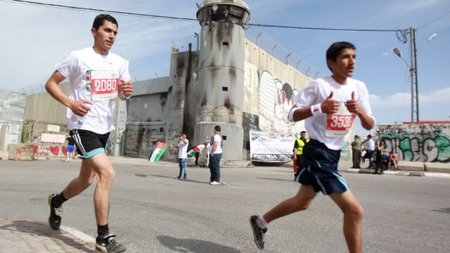 رياضيون فلسطينيون عرب واجانب يركضون على طول الجدار الاسرائيلي المثير للجدل  الثالث ماراثون فلسطين الثالث في  بيت لحم 27 مارس 2015. ووفقا لمسؤولين فلسطينيين قد شارك حوالي 3200 عداء في سباق الماراثون هذا العام  AFP PHOTO / MUSA AL SHAER
