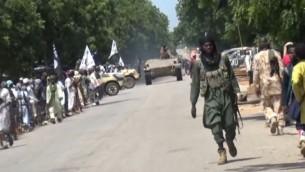 صورة استخرجت من شريط فيديو نشره تنظيم بوكو حرام وحصلت عليه وكالة فرانس برس يظهر مقاتلي بوكو حرام يعرضون دبابة في قرية غير معروفة (AFP/HO/BOKO HARAM)