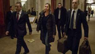 وزيرة خارجية الإتحاد الأوروبي فيديريكا موغيريني، في الوسط، تصل إلى فندق بو ريفاج بالاس في 28 مارس، 2015، في لوزان، سويسرا، خلال المحادثات النووية مع إيران. (AFP/POOL/BRENDAN SMIALOWSKI)
