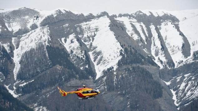 مروحية اغاثة فرنسية تحلق بالقرب من موقع تحطم طائرة ايرباص ايه-320 في جبال الالب، 24 مارس 2015 (ANNE-CHRISTINE POUJOULAT / AFP)