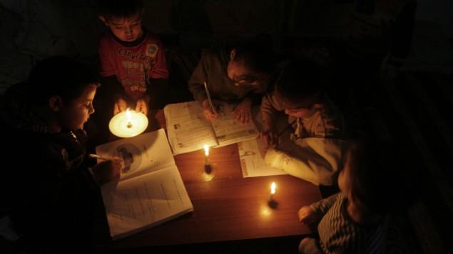 اطفال فلسطينيون يدرسون على نور الشموع بسبب انقطاع الكهرباء في مخيم اللاجئين رفح، جنوب قطاع غزة، 9 نوفمبر 2013 (Abed Rahim Khatib/Flash90)