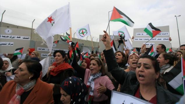 نساء فلسطينيات يحيون يوم المرأة العالمي بمظاهرة في حاجز قلنديا، 8 مارس 2015 ( Issam Rimawi/Flash90)