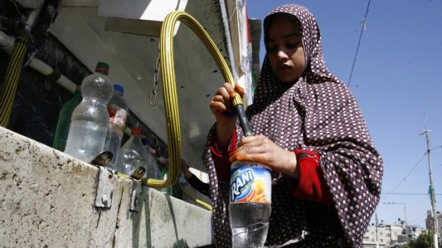 فتاة فلسطينية تعبئ المياه من منشأة الأونروا في مخيم اللاجئين رفح، جنوب قطاع غزة، 6 ابريل 2014 (Abed Rahim Khatib / Flash90)
