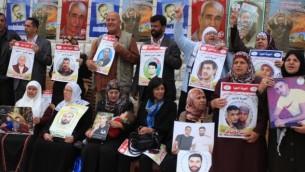فلسطينيون يحملون صور اقربائهم المعتقلين في السجون الإسرائيلية خلال مظاهرة امام مكتب الصليب الأحمر في رام الله، 15 ابريل 2014 (Issam Rimawi/FLASH90