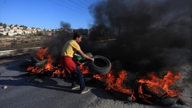 شاب فلسطيني من مخيم الجلزون للاجئين يضع إطارات مشتعلة على الطريق المؤدي إلى مستوطنة بيت إيل بالقرب من رام الله خلال اشتباكات مع جنود إسرائيليين، 24 أكتوبر، 2014. (STR/Flash90)