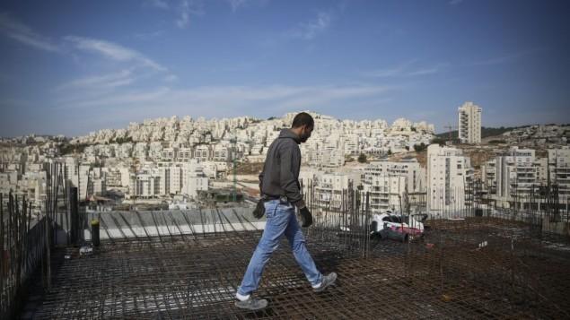 عامل بناء بالقرب من حي هار حوما في القدس الشرقية في أكتوبر، 2014. (Hadas Parush/Flash90)