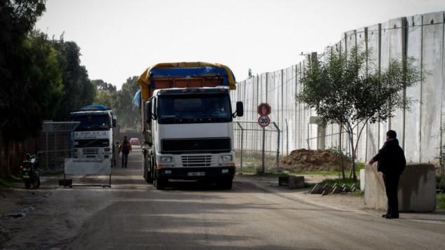 شرطي فلسطيني بجانب شاحنة تحمل الاسمنت، دخلت غزة من اسرائيل عن طريق معبر كرم ابو سالم في رفح، جنوب قطاع غزة، 25 نوفمبر 2014 (Abed Rahim Khatib / Flash90)