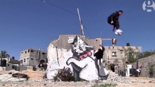 """لاعب باركور من غزة يعرض مهاراته امام جدارية للفنان البريطاني """"بانكسي"""" في مدينة غزة (screen capture: Youtube/The Guardian)"""