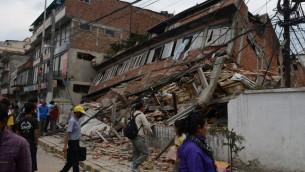 أشخاص يتفحصون الأنقاض في كاتماندو، عاصمة النيبال، التي تضررت بشدة من الزلزال المدمر في 25 أبريل 2015 (PRAKASH MATHEMA / AFP)