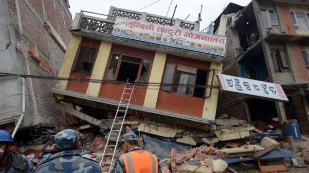 طواقم اسعاف نيبالية امام مباني مدمرة في كاتماندو، عاصمة النيبال، 26 ابريل 2015 (PRAKASH MATHEMA / AFP)