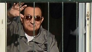 الرئيس المصري السابق حسني مبارك يلوح لمؤيديه من شرفة غرفته في مستشفى المعادي العسكري في القاهرة في 29 نوفمبر، 2014. ( AFP/AL-WATAN NEWSPAPER/MOHAMED NABIL)
