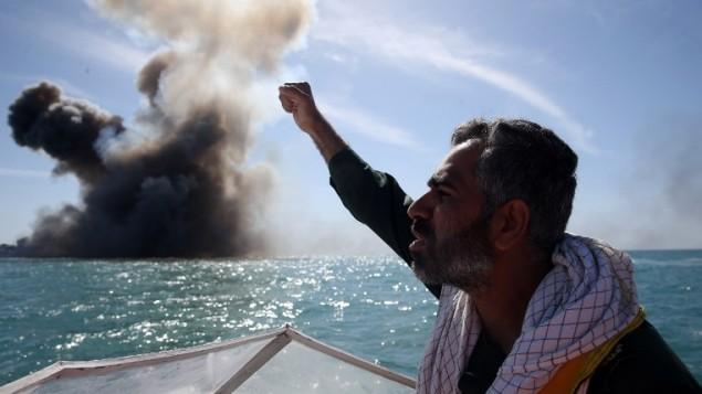 أحد عناصر الحرس الثوري الإيراني يردد شعارات بعد مهاجمة سفينة حربية خلال تدريبات عسكرية في مضيق هرمز جنوب إيران، 25 فبراير، 2015. ( Hamed Jafarnejad/AFP/Fars News)