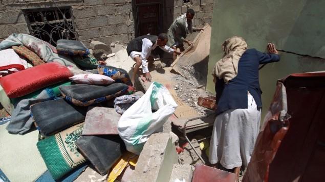يمنيون يبحثون بين حطام منزلهم بالقرب من مطار صنعاء، 31 مارس 2015 (MOHAMMED HUWAIS / AFP)