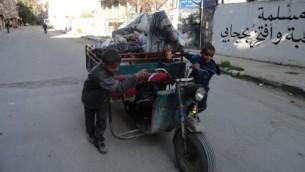 اطفال مع عربة محملة في شوارع مخيم اليرموك، 4 ابريل 2015 (RAMI AL-SAYED / AFP)
