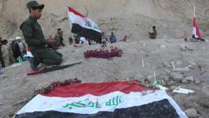مقاتل عراقي شيعي يصلي في موقع يعتقد انه مقبرة جماعية لضحايا مجزرة سبايكر في مدينة تكريت العراقية، 4 ابريل 2015 (AHMAD AL-RUBAYE / AFP)