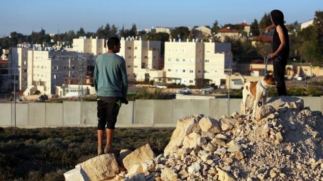 صورة توضيحية، اطفال فلسطينون من مخيم الجلزون للاجئين يطلون من وراء الجدار على مستوطنة بيت ايل، في الضفة الغربية 7 أبريل، 2015. AFP PHOTO/ABBAS MOMANI