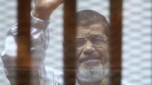 ارشيف - الرئيس المصري السابق محمد مرسي داخل قفص خلال محاكمته في القاهرة، 7 ديسمبر 2014 (AHMED RAMADAN / AFP)