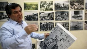 سيروب ساهاغيان، مدير نادي الهومنتمن، يعلق  صور في معرض لاحياء الذكرى المئوية للإبادة الأرمنية من قبل الامبراطورية العثمانية عام 1915، القدس، 17 ابريل 2015 (AFP PHOTO / GALI TIBBON)