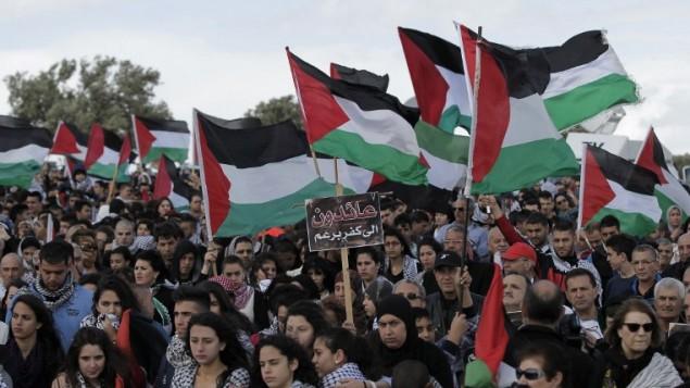 الالاف من مواطني اسرائيل العرب يحملون الأعلام الفلسطينية خلال مسيرة العودة السنوية من اجل حق العودة للاجئين الفلسطينيين الذين فروا من ديارهم أو طردوا خلال حرب عام 1948. مسيرة هذا العام الى قرية الحدثة بالقرب من طبريا في شمال إسرائيل،  23 أبريل عام 2015. AFP PHOTO / AHMAD GHARABLI