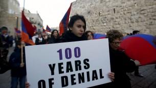 أفراد من الطائفة الأرمنية يسيرون مع أعلام ومشاعل في 23 ابريل، 2015 في البلدة القديمة في القدس، عشية إحياء الذكرى المئوية لمذبحة الأرمن في فترة الإمبراطورية العثمانية في 1915. ( AFP/Gali Tibbon)