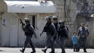 طفلة فلسطينية ورجل فلسطيني يقفون بينما يعبر عناصر قوات الامن الاسرائيلي خلال الموجهات في حي الطور بعد ان قتلت الشرطة فلسطيني يبلغ ال 17 من العمر 25 ابريل 2015  AFP PHOTO / AHMAD GHARABLI
