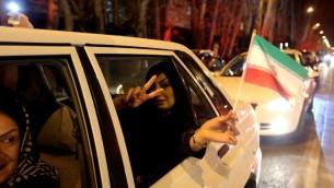 امرأة ايرانية تحتفل مع  العلم الإيراني في شارع فلييسر في شمال طهران 2 أبريل عام 2015، بعد الإعلان عن اتفاق بشأن المحادثات النووية الايرانية.. AFP PHOTO / ATTA KENARE