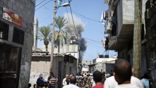 فلسطينيون يراقبون سحابة الدخان المتصاعد فوق المنازل بعد لحظات من سقوط صاروخ إسرائيلي في أرض مفتوحة بالقرب من مدينة غزة في 21 أغسطس، 2014. ( AFP/ ROBERTO SCHMIDT)
