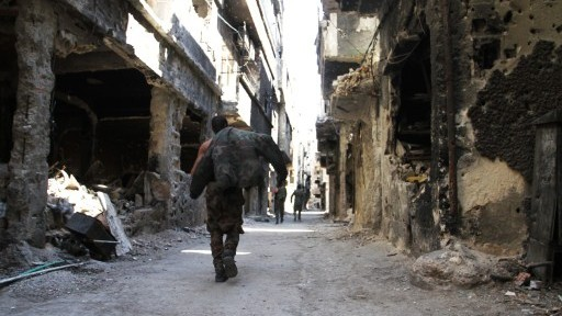 جندي يمشي بين المباني المهدمة في مخيم اليرموك للاجئين الفلسطينيين، 6 ابريل 2015 (YOUSSEF KARWASHAN / AFP)