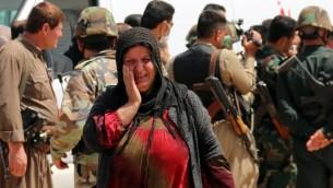 امرأة ايزيدية تبكي عند وصولها قرية الحميرة، بعد اطلاق سراح الدولة الإسلامية لأكثر من 200 ايزيديا، 8 ابريل 2015 (MARWAN IBRAHIM / AFP)