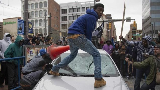 متظاهرون يكسرون زجاج سيارة شرطة في بالتيمور، الولايات المتحدة، خلال الاحتجاجات على مقتل فريدي غراي، 25 ابريل 2015 (JIM WATSON / AFP)