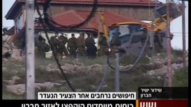 الجنود الإسرائيليون خارج قرية بيت عينون، بالقرب من الخليل، في الضفة الغربية، خلال عمليات بحث عن شاب إسرائيلي اختفى في 2 أبريل، 215. (لقطة من Channel 2)