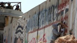 صورة توضيحية لناشط يكتب شعارات على الجدار الفاصل بالقرب من حاجز قلنديا بين رام الله والقدس (Issam Rimawi/Flash90)