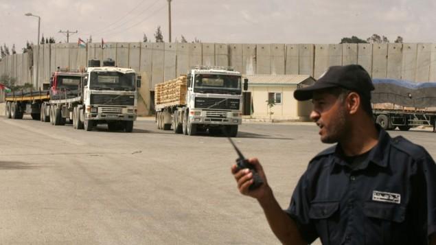 شرطي فلسطيني تابع لحماس يشرف على شاحنات تدخل مواد بناء الى قطاع غزة عن طريق معبر كرم ابو سالم، 22 سبتمبر 2013 (Abed Rahim Khatib/Flash90)