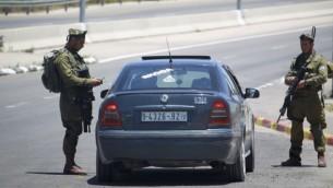 جنود اسرائيليون يفتشون سيارة فلسطينية في مفترق غوش عتصيون في الضفة الغربية، 16 يونيو 2014 (Hadas Parush/Flash90)