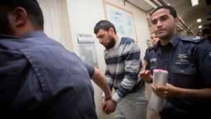 الشرطة ترافق خالد قطينة، العربي من اسرائيل الذي دهس مشاة يهود في القدس، الى المحكمة المركزية في القدس، 16 ابريل 2015 (Miriam Alster/FLASH90)