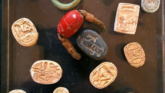 مجموعة من السلالة ال 18 تشمل قطع أثرية تضم أختام  فرعونية  وخاتم عقيق مختوم تم العثور عليها في كهف بالقرب من تل حليف، جنوب إسرائيل، على يد سلطة الآثار الإسرائيلية. 1 ابريل 2015  (Ilan Ben Zion/Times of Israel staff)