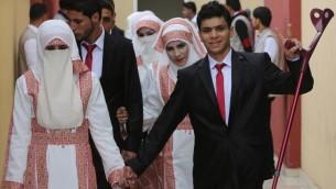 العروس الفلسطينية مروى موسى وعريسها احمد ابو سلامة يشاركان في حفل الزواج الجماعي في مدينة غزة، 11 ابريل 2015 (AFP/ MAHMUD HAMS)