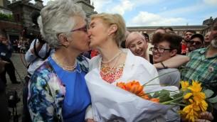 عضوة مجلس الشيوخ الايرلندي كاثرين زابون تقبل شريكتها ان لويس غيليغان اثناء انتظار داعمي الزواج المثلي لنتائج الاستفتاء في دبلين، 23 مايو 2015 (PAUL FAITH / AFP)