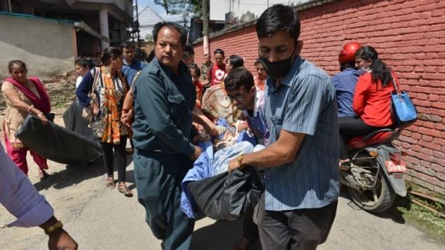 نقل مرضى نيباليين خارج مبنى أحد المستشفيات بعد أن ضرب زلزال بقوة 7.3 درجات البلاد، في كاتماندو يوم الثلاثاء، 12 مايو، 2015. (AFP PHOTO / PRAKASH MATHEMA)