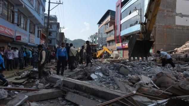 طواقم انقاذ ومارين يبحثون عن الناجين تحت انقاض بيت منهار في كاتماندو عاصمة النيبال، 12 مايو 2015 (PRAKASH MATHEMA / AFP)