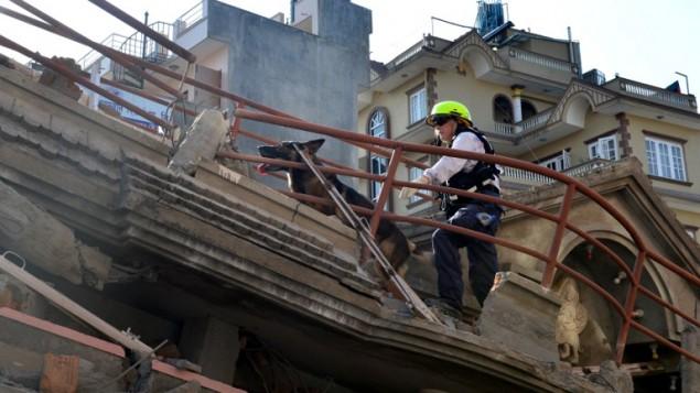 طاقم اغاثة امريكي يبحث عن الناجين تحت انقاض مبنى منهار في كاتماندو عاصمة النيبال، 12 مايو 2015 (PRAKASH MATHEMA / AFP)
