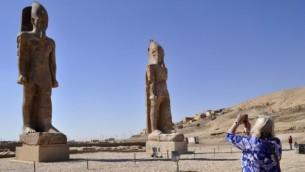 سائحة تلتقط صورة لتمثالين ضخمين للفرعون أمنحتب الثالث في المعبد الشهير في  مدينة الأقصر المصرية، 14 ديسمبر، 2014. (AFP/Radwan Abu Elmagd)
