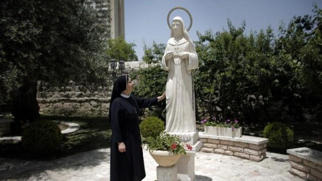 """راهبة بجانب تمثال لماري الفونسين غطاس في دير """"راهبات الوردية"""" في القدس، 12 مايو 2015 (AHMAD GHARABLI / AFP)"""