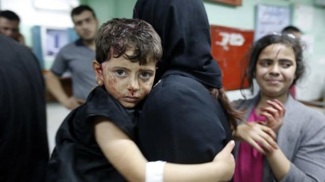 امرأة فلسطينية تحمل طفلها المصاب داخل مستشفى في بيت لاهيا بعد وقوع انفجار في مقر تابع لحماس، 14 مايو 2015 (MOHAMMED ABED / AFP)