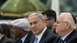 رئيس الوزراء بينيامين نتنياهو (في الوسط) والرئيس رؤوفين ريفلين (من اليمين) يشاركان في حفل في جبل هرتسل بمدينة القدس لإحياؤ ذكرى اليهود الأثيوبيين الذين قُتلوا خلال الهجرة إلى إسرائيل، 17 مارس، 2015. (AFP/Baz Ratner, Pool)