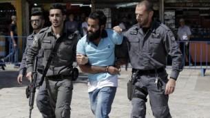 اعتقال متظاهر فلسطيني من قبل القوات الإسرائيلية خلال مسيرة العلم في البلدة القديمة في القدس، 17 مايو 2015 (AFP Photo/Jack Guez)