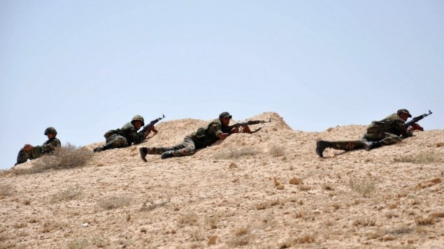 جنود سوريون خلال القتال ضد تنظيم الدولة الإسلامية في تدمر، 17 مايو 2015 (AFP/STR)
