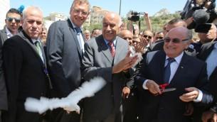 رئيس الفيفا جوزيف بلاتر، من اليمين، يطلق حمامة وسط تصفيق رئيس إتحاد كرة القدم الفلسطيني جبريل رجوب، في المركز، خلال زيارته إلى قرية دورا القرع، بالقرب من مدينة رام الله في الضفة الغربية، في 20 مايو، 2015. (AFP/ABBAS MOMANI)